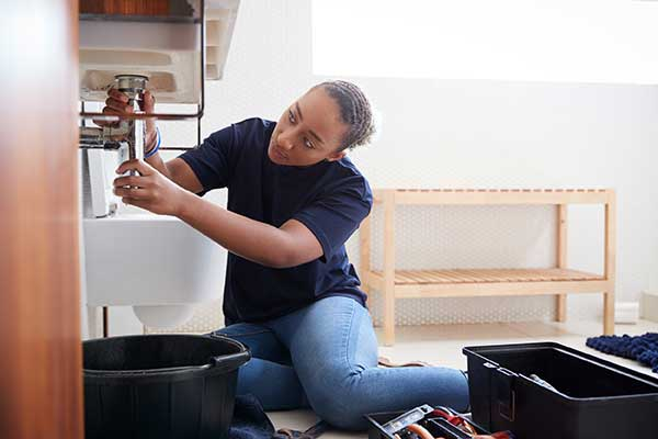 Nonrenewable Energy Resources Conserving - Lady fixing plumbing